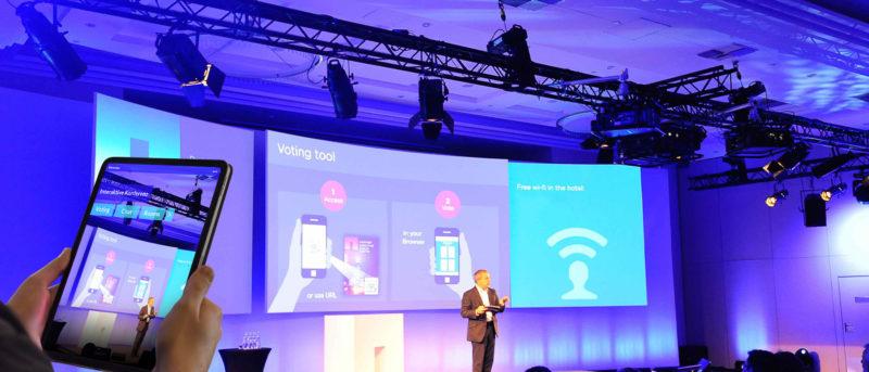 Interaktive Konferenz, Mann auf Bühne und Mann mit iPad, commacross