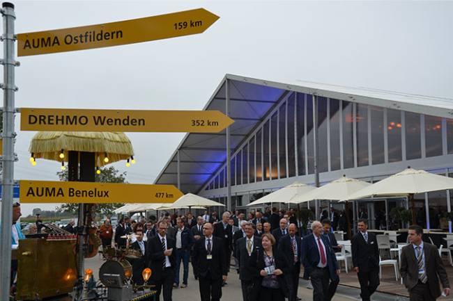 Der Wegweiser zeigt zu allen AUMA Standorten. Im Hintergrund laufen viele Besucher.