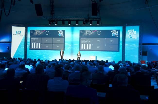 Moderatoren auf Buehne, Publikum benutzt eine digitale Voting-App zur Abstimmung. Digitale Interaktion zwischen Moderator und Publikum