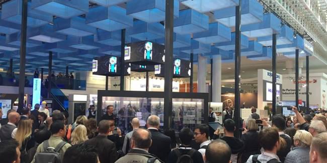 Messeshow mit sechs großen transparenten Displays, einem Moderator und begeisterten Zuschauern auf dem Messestand