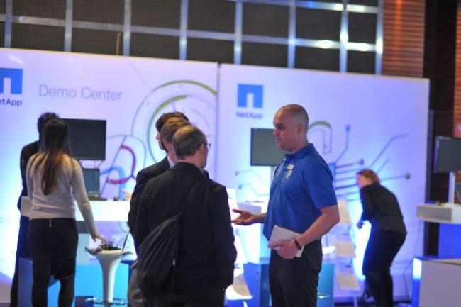 Ein NetApp Mitarbeiter berät professionell einige Interessenten im Demo Center.