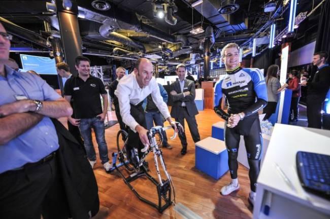 Ein Gast testet ein Rennrad und betrachtet seine Ergebnisse auf einem Bildschirm. Er wird von einem Profi-Radfahrer und Zuschauern beobachtet.