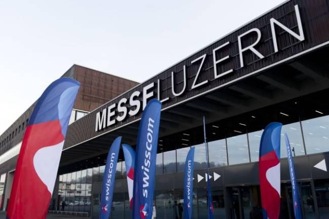 Aussenansicht der Messe Luzern mit Swisscom gebrandeten Fahnen davor.