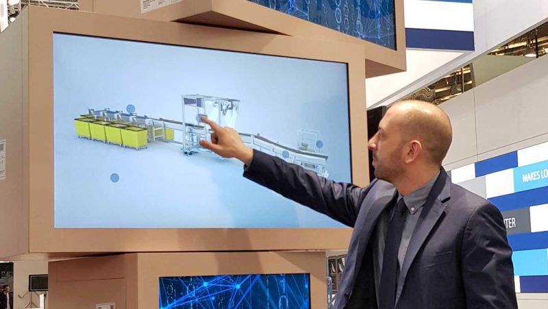 Mann toucht durch eine interaktive Produktpräsentation auf einem Messestand.